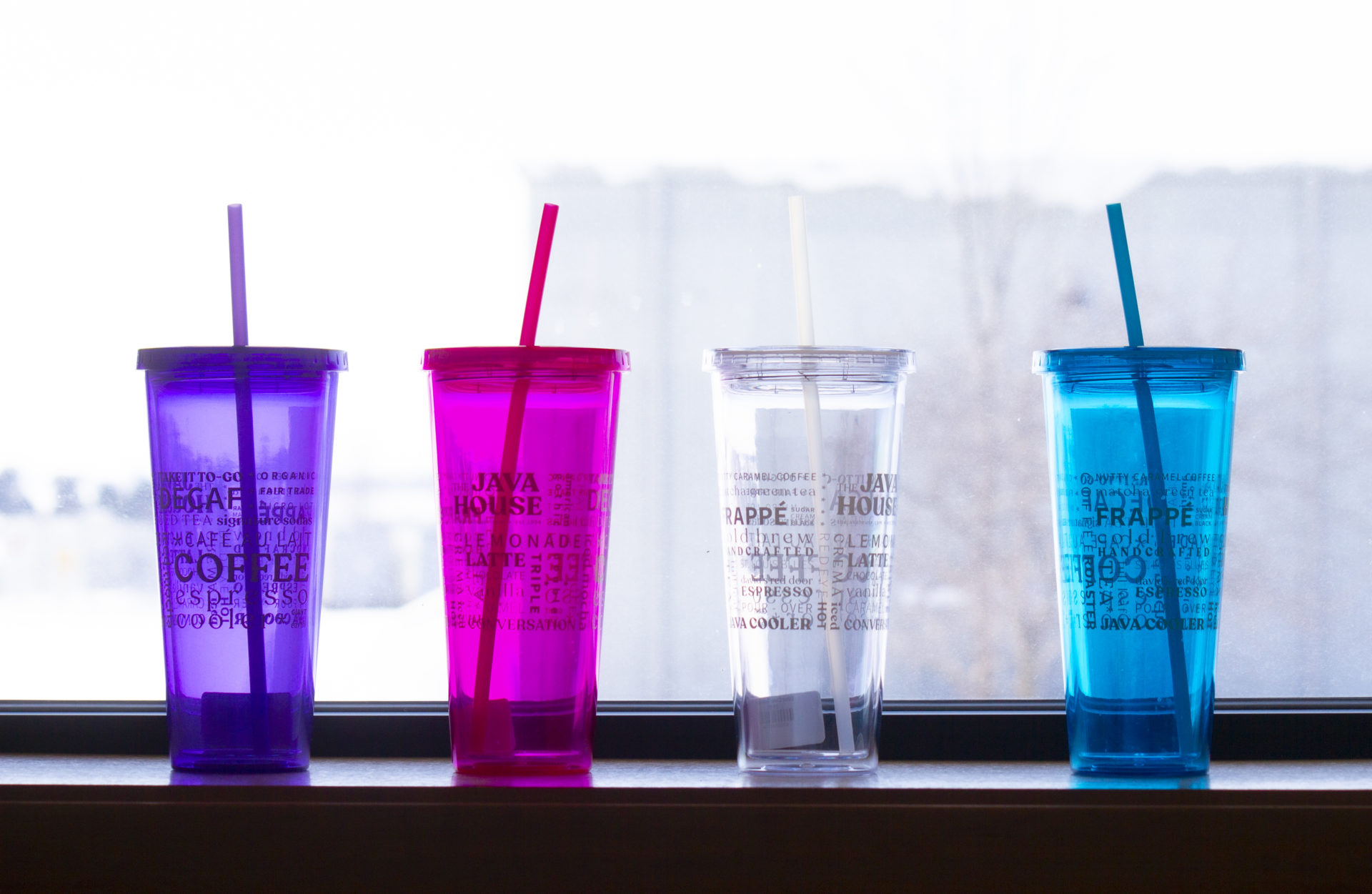 4 translucent tumblers in a window sill, they are purple, pink, clear, and blue.