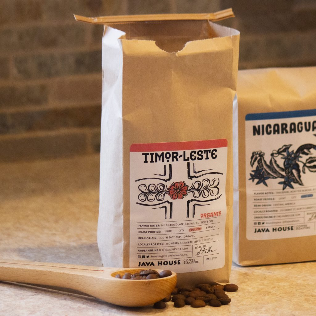 a bag of timor-leste in a brown kraft bag, with coffee beans in the foreground