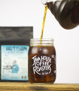 cold brew being poured into a Java House Coffee roaster mason jar, a back of artisan cold blend beans is in the background